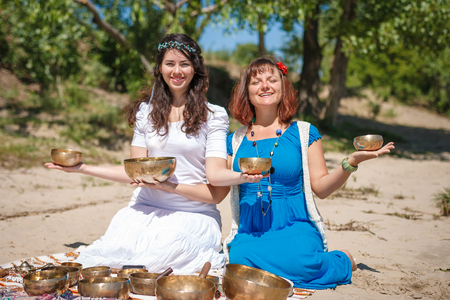 Two young beautiful women playing tibetan singing bowls in nature on the river bank at spring sunny day Stock Photo