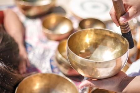 Woman playing a singing bowls also known as Tibetan Singing Bowls, Himalayan bowls. Making sound massage at beautiful sunny day.