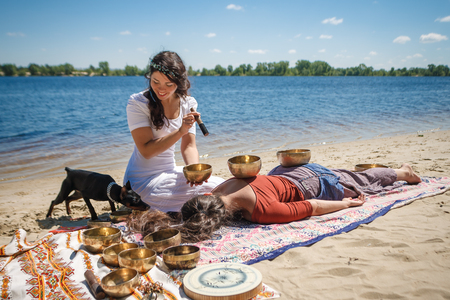 Beautiful female receiving energy sound massage with singing bowls on her body on a river bank at spring sunny day. And little black doggy interested in