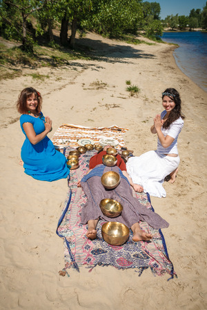 Beautiful female receiving energy sound massage with singing bowls on her body on a river bank at spring sunny day Stock Photo