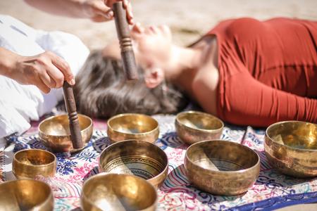 여자는 노래 그릇 티베트 노래 그릇, 히말라야 그릇으로 알려진 연주. 아름 다운 화창한 날에 사운드 마사지를 만들기.