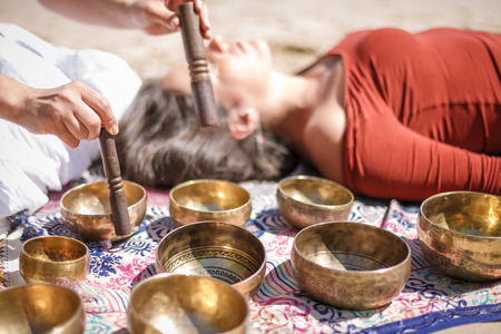 Vrouw die een zangschaal speelt, ook bekend als Tibetaanse Zangbakken, Himalayan Bowls. Klankmassage maken op mooie zonnige dag.