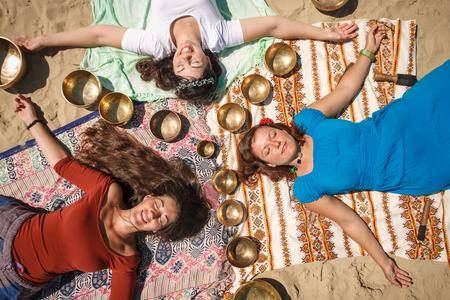 Three beautiful females lying down as a mandala with singing bowls on a river bank at spring sunny day