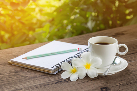 Coffee and a notebook on wooden table with warm sunlight in a garden