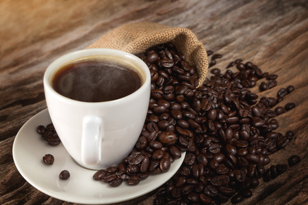 A cup of hot coffee on a wooden table with roasted coffee beans Standard-Bild