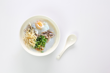 Congee or Rice porridge with slice ginger, egg, pork in a bowl on white background