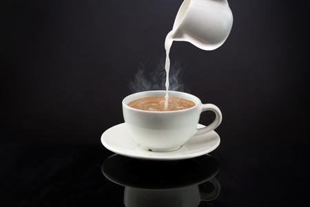 Gießen in einen heißen Kaffee oder Tee mit Dampf auf schwarzem Hintergrund