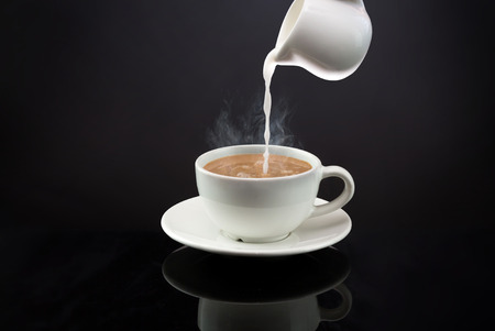 Pouring into a hot coffee or tea with steam on black background Foto de archivo