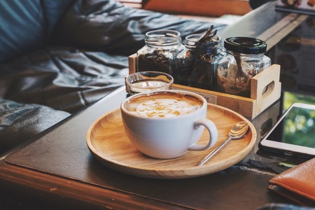 Relaxing time with hot latte coffee in white mug on wooden table in a coffee cafe