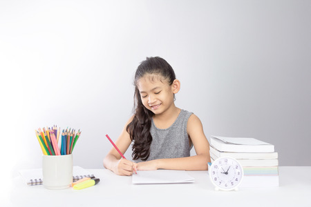 Little asian kid doing homework or drawing at home with smling face Zdjęcie Seryjne