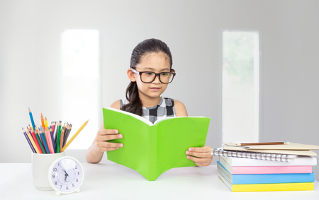 Cute little asian girl wear glasses reading book with stack of book on table a concept for education Zdjęcie Seryjne
