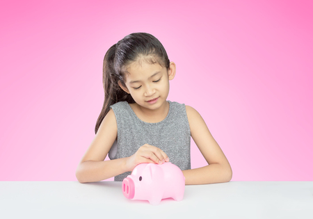 Asian girl age around 8 years old putting coin into pink piggy bank on pink background with clipping path