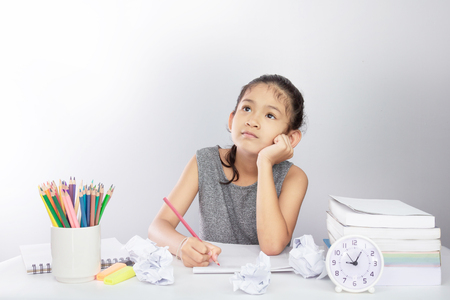Cute asian girl thinking hard of doing her home work with crumpled paper on a table