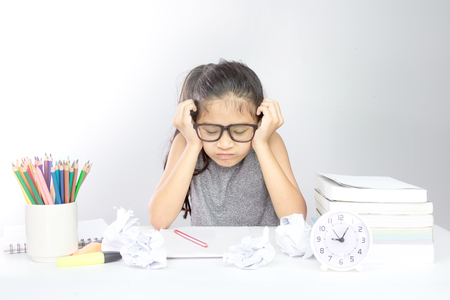 Stressed young asian girl with her head in hands looking homework and crumpled Paper on the desk