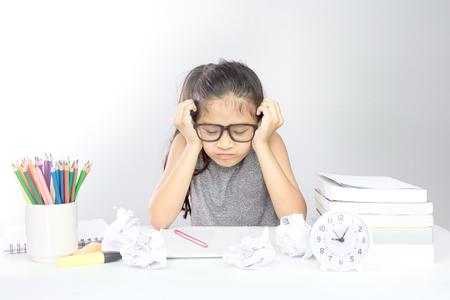 Destacó a joven asiática con la cabeza entre las manos mirando los deberes y papel arrugado sobre el escritorio