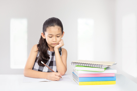 Cute asian kid concentrate on her homework a concept for education Imagens
