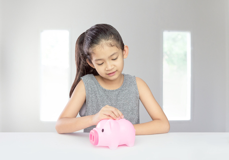 Cute asian girl putting coin into piggy bank saving money for her future concept for financial