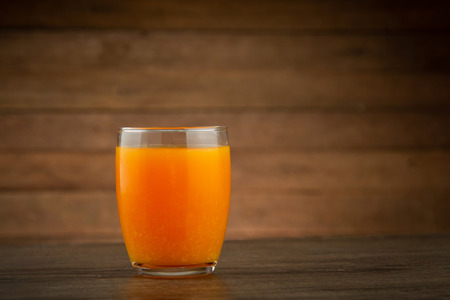 A glass of orange juice on wooden table Imagens