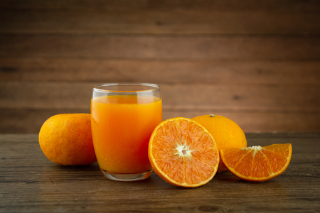 A glass of orange juice and a slice of orange fruit on wooden table