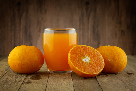 Glass of fresh orange juice on vintage wood table with copy space Imagens