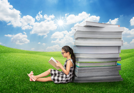 Young asian girl reading book on green grass field in summer blue sky with big stack of books on her back for education concept