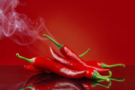 Red hot chillies on red background with reflection and smoke a concept for hot and spicy food 写真素材