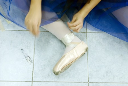 pointes: repair Ballet shoes  wear ballet dancer wears pointes, sitting on the floor