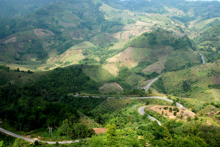hill range: Road through high mountain range. Areal view on road going on top of the hill through high mountains with green forests, Chiang Rai, northern Thailand Stock Photo