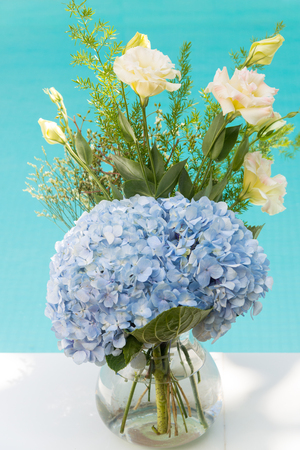 pasto sintetico: Beautiful bouquet of light blue  flower with the blue sky pool background  in luxury hotel, thailand