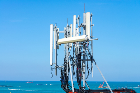 Phone   telecommunication antenna on building with blue sea and sunny sky day  in pattaya beach, thailand