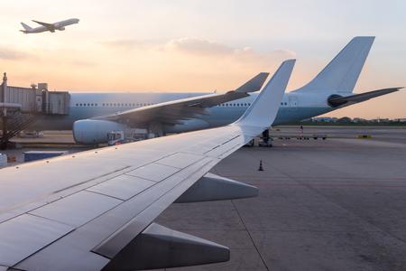夕日を背景に離陸する飛行機の窓からの眺めの空港や航空機の交通のタクシー レーンで滑走路に待機している飛行機ジェット