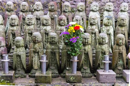 Japanese smile stone buddha monk statue (Jizo Bosatsu), Japanese believe that they can help protect tourists and children to survive, Hasedera Temple, Kamakura, Japan Standard-Bild - 94220116