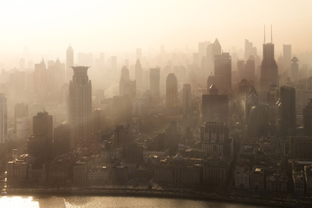 Smog lies over the skyline of Historical architecture and modern skyscraper on the bund of Shanghai city in misty sunrise, Shanghai, China vintage picture style