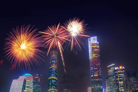 Celebration firework in twilight night cityscape of guangzhou urban skyscrapers at storm with lightning  bolts in night purple blue sky, Guangzhou, China Stock Photo