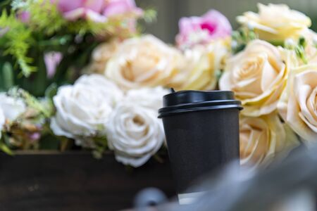 Paper coffee cup on bouquet of flowers and green outdoor background Фото со стока - 147459752