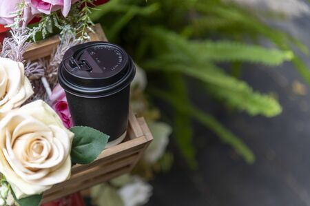 Paper coffee cup on bouquet of flowers and green outdoor background