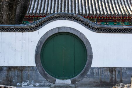 Green circle Chinese wood door and wall in traditional garden, forbidden City, Beijing, China