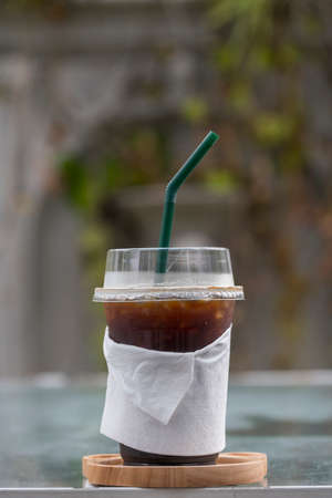 Iced Americano coffee in take home plasttic cup on glass tablewith green outdoor background