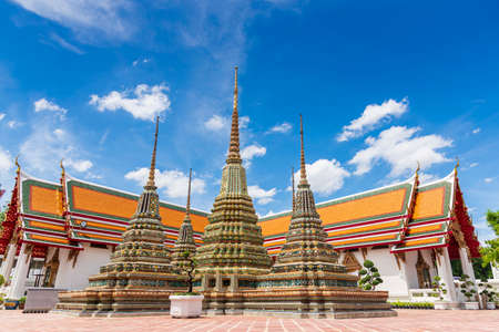 Ancient buddhist stupas and pagoda at Temple of Reclining Buddha (Wat Pho) with blue sky in Bangkok city, Thailand Stock Photo