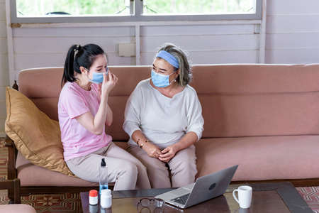 Asian young woman teach older mother, how to wear face mask from online learn in living room with carefully. family concept