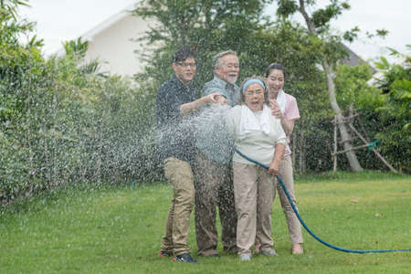 Asian family feel haapy with smil lovely are watering a tree by tube in garden at outdoor house in morning.