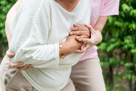 Asian female woman take care and support Elder Asian senior female suffering heart attack from heartbeats symptoms of chest pain, coronary artery disease causes from high blood pressure - heart disease, health problem and insurance