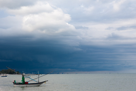 storm coming: small fishing boat on the sea Storm is coming Stock Photo