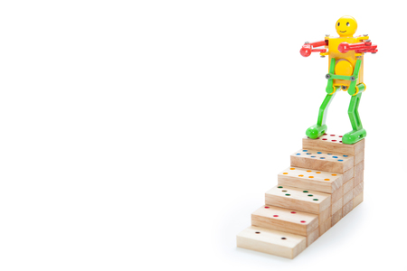 robot toy standing on top steps of  wooden domino, on white background, clipping path. copy space of your text Stock Photo