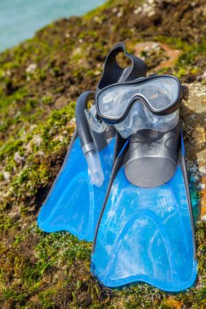 Swim flippers, mask, snorkel on  rock moss beach sea and blue sky Stock Photo