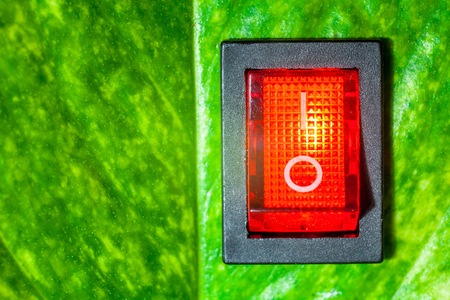 Red power switch on green leaves save World concept friendly energy saving