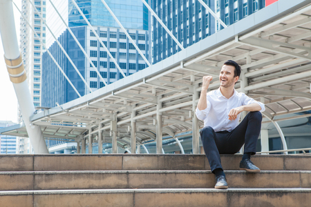 happy business man smiling and commitment to success sitting on stair in downtown