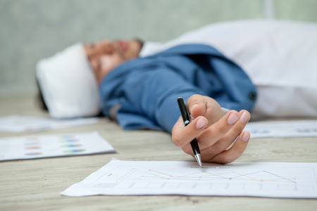 Business man Fainted On Floor In Office. Unconscious Young Businessman Lying with Graphs and charts work hard Stock Photo