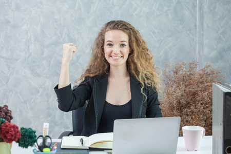 happy business woman arm up celebrating working successful in office