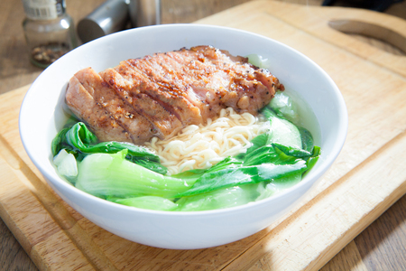 Instant Noodles with fried Pork Cutlet with Pak Choy or Chinese Cabbage in white bowl and Plate on wooden table Stock Photo